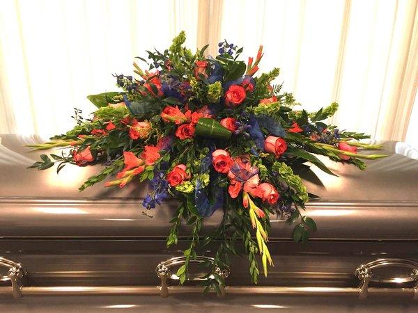 orange roses and dark blue delphinium casket spray